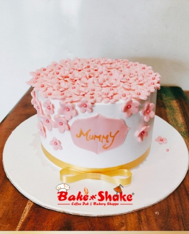A CAKE WITH SMALL PINK FLOWERS